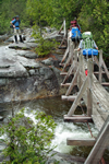 backpackers crossing bridge